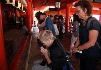 宮島の厳島神社で手を合わせるフェルフールトさん(手前左)=広島県廿日市市で、高尾具成撮影