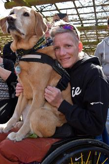 生活に欠かせないパートナーの介助犬「ゼン」を抱くフェルフールトさん=ベルギー東部ハッセルトで4月、八田浩輔撮影