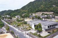 県庁から鳥取城跡を望む。天球丸の石垣の下、鳥取西高校の校舎が建ち並ぶ高まり(中央から右)が三ノ丸。右端のクレーン車のあたりに籾蔵が並んでいた=鳥取市で、園部仁史撮影