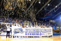 「B1最短昇格決定!」の横断幕を掲げる選手ら=松江市学園南1の市総合体育館で、根岸愛実撮影