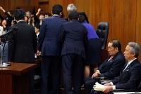 衆院法務委員会で「共謀罪」法案の採決を巡って委員長席に野党議員らが詰め寄る中、採決を待つ金田勝年法相(右から2人目)=国会内で2017年5月19日午後1時9分、小川昌宏撮影
