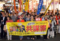 Demonstrators march down a street against the