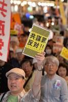 A man raises a sign reading