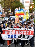 People parade down a street in Sapporo's Chuo Ward against the