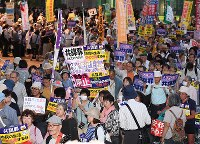 Demonstrators are seen parading down a street in Nagoya's Naka Ward against the