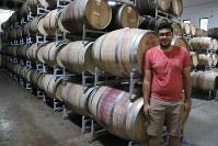 ワインの原液が詰まった樽の前に立つカラン・バサニさん=インド中部ナーシクのスーラ・ビンヤーズで、金子淳撮影