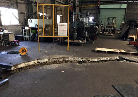 熊本地震の本震で工場の床に地割れが走り、約20センチの段差が生じた富田鉄工=同社提供.jpg