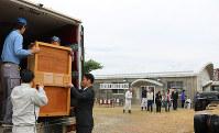 ツルの入った木箱をトラックに載せる関係者