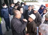玄海町役場の前で職員と向き合う新さん(右奥から2人目)たち
