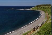 日本海の海岸線を走る快速「リゾートしらかみ」号。日中も良いが夕景はまさに絶景だ=青森県の五能線・追良瀬(おいらせ)―驫木(とどろき)駅間で、村上悠太さん撮影