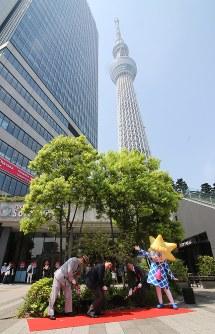 開業5周年を記念し、墨田区の花ツツジの一種「ミツバツツジ」を植える東京スカイツリー公式キャラクター「ソラカラちゃん」(右)や関係者ら=同区押上1で