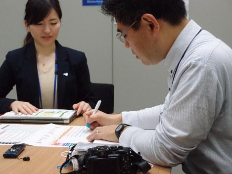 健康運動指導士の小野さん(左)との最終面談で、分析シートを使いながら目標達成を確認する太田