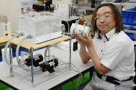 ファインバブルを発生させるノズルを持つ、秦隆志・高知高専准教授=高知県南国市物部乙で、柴山雄太撮影