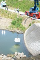 堤防を補強するため、川にコンクリートブロックを投入する訓練