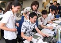 「クールビズ」が始まりアロハシャツで仕事をする環境省の職員=東京・霞が関で1日、藤井達也撮影