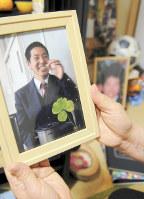 山内美輝さんの遺影を手にする母の千恵子さん。遺影には四つ葉のクローバーが添えられていた=兵庫県尼崎市で、茶谷亮撮影