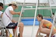 試合中に父・馬淵崇英コーチ(左)からアドバイスを受ける馬淵優佳=那覇市の奥武山水泳プールで2010年8月19日、野田武撮影