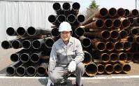 製造加工した鉄製電柱を背にする呉山良雄さん。今も現場では作業服を着る=滋賀県湖南市石部口2の伸和工業で、大澤重人撮影