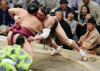 Yokozuna Harumafuji is forced over the straw bales by komusubi-ranked grappler Mitakeumi to suffer his first loss of the May Grand Sumo Tournament, on May 24, 2017, Day 11 of the 15-day competition. (Mainichi)