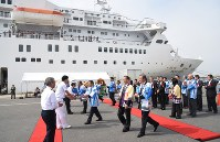 寄港した大型客船「ぱしふぃっくびいなす」の前で、乗員らを笑顔で歓迎する地元関係者ら=石巻港で