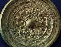 三角縁神獣鏡。縁の断面が三角形で、メインの文様は中国の不老長寿の思想を表す。鈕(ちゅう、中央の半球体)の周りに東王父{とうおうふ}・西王母{せいおうぼ}と2頭の獣を対置し、四神文帯(玄武・朱雀・青龍・白虎)には「天・王・日・月」の銘文がある。3世紀、18号遺跡出土(宗像大社所蔵)=福岡県宗像市の宗像大社で2017年5月17日、森園道子撮影