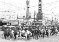 恵美須交差点で安保反対を叫んで気勢を上げるデモ隊。路面電車の車両と線路が見える=1960年5月26日撮影