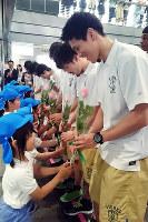 園児から花を手渡される西宮ストークスの選手=兵庫県芦屋市役所で、山本愛撮影