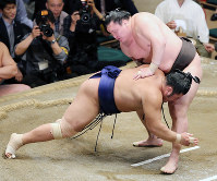 Yokozuna Hakuho, right, forces maegashira No. 4 Tochiozan into the dirt to stay undefeated on Day 12 of the May Grand Sumo Tournament, on May 25, 2017. (Mainichi)