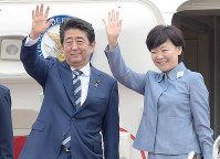 Prime Minister Shinzo Abe and his wife Akie wave before boarding a government plane at Tokyo's Haneda Airport on May 25, 2017, to attend a two-day G-7 Summit in Taormina, Italy, as well as make a state visit to Malta. (Mainichi)