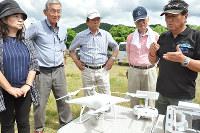 ドローンを前に、飛ばし方を話す中谷克次さん(右端)と、説明を聞くNPOのメンバーたち=福井県永平寺町で、大森治幸撮影