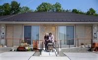 2人で1台の手押し車を押し、散歩に出かける鈴木ふちいさん(右)と星操さん。天気が良く、体調がすぐれている時の日課だ。右はふちいさんの自宅、左は星さんの自宅=宮城県山元町の町営桜塚住宅で2017年5月18日、小川昌宏撮影