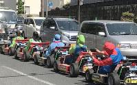キャラクターの服を着て、連なって走る公道カート=大阪市中央区で、堀江拓哉撮影
