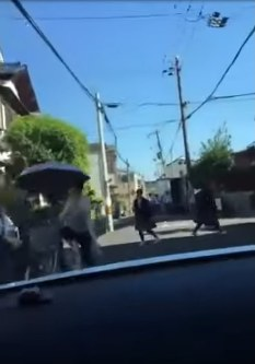 A screenshot of video footage of people trying to avoid the high-speed car in the city of Kadoma in Osaka Prefecture, on May 19, 2017, is shown here. (Image from YouTube)