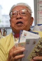 はがきを手に当時を振り返る西山進さん=福岡市南区で、矢頭智剛撮影