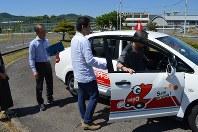男性(68)=右端=の実車評価を始める指導員の横山喜孝次長(左端)と、同乗する作業療法士の酒井英顕さん=岡山自動車学校教習所で