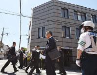 警察官が警戒する中、会合のため事務所に入る「任俠団体山口組」の関係者ら=兵庫県尼崎市で2017年5月28日午後1時39分
