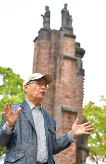 Takashi Yamakawa, 80, reflects on his work sharing his experiences during the atomic bombing of Nagasaki against the backdrop of the remains of Urakami Cathedral in Nagasaki Peace Park in Nagasaki, on April 27, 2017. (Mainichi)