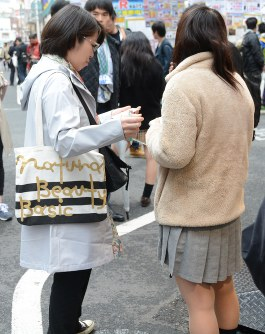 A Metropolitan Police Department officer, left, asks for the age of a girl working for a JK business in Tokyo's Akihabara district in April 2017. (Mainichi)