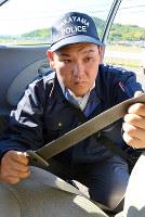 シートベルトの圧着痕を調べる岡雅史警部補=和歌山市西の県警交通センターで、最上和喜撮影