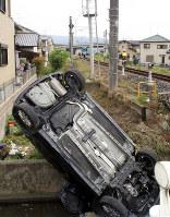 電車(中央奥)と衝突し、側溝に転落した乗用車=奈良県桜井市金屋で2017年5月30日午後3時24分、山本和良撮影