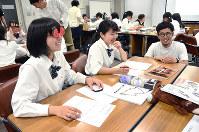 イチゴ型の眼鏡をかけてデザインを考えるJK課のメンバー=福井県鯖江市役所で、立野将弘撮影