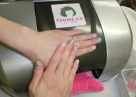 爪にネイルアートを印刷するプリンター「ツメコ」。プリンターの開口部に手を入れて印刷する=東京都品川区の千趣会本社で2017年5月26日、今村茜撮影