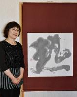 毎日書道展新会員作家展に出品した「熱」を前に「イメージ通りの美しい墨色が出たときはうれしい」と話す西本佳奈さん=松山市で、成松秋穂撮影