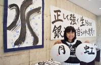 作品の前で笑顔の森本莉世さん。「水」は、宮沢賢治の「やまなし」をイメージしてモップで書いた=奈良市のギャラリー「GM-1」で、塩路佳子撮影