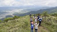 加悦谷平野をバックに記念写真。大江山連峰の尾根から眺める景色は格別だ=京都府与謝野町、大江町にまたがる鳩ケ峰の頂上近くで、安部拓輝撮影