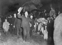 雨の中で手を振る昭和天皇。戦後の全国巡幸では各地で歓迎を受けた=福井県・河和田村(現鯖江市)で1947年10月撮影