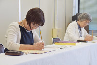 原爆死没者名簿に、新たに判明した死者の名を書き込む森田孝子さん(左)と竹内絹子さん=長崎市役所で2017年6月5日午前10時15分、浅野翔太郎撮影