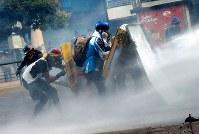治安部隊の放水に抵抗する反政府デモ隊=カラカスで2017年5月20日午後4時31分、朴鐘珠撮影