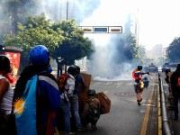 治安部隊に向けて火炎瓶を投げようとしている反政府デモ隊の若者(右)=カラカスで2017年5月20日午後4時11分、朴鐘珠撮影