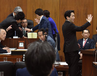 Opposition party lawmakers surround the seat of the head of the lower house Committee on Judicial Affairs, left, in protesting a vote on the so-called anti-conspiracy bill, on May 19, 2017. Pictured on the far right is Justice Minister Katsutoshi Kaneda. (Mainichi)